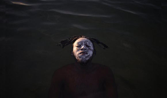 African Refugee of the Democratic Republic of Congo swimming on his back in the waters of guanabara bay, Rio de Janeiro