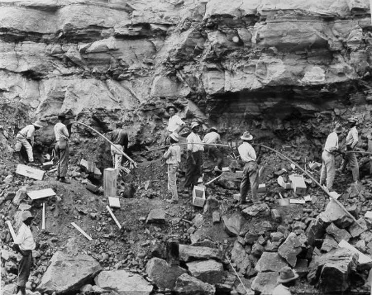 Loading shot holes with dynamite to blast a slide of rock in the west bank of the Culebra Cut, February 1912