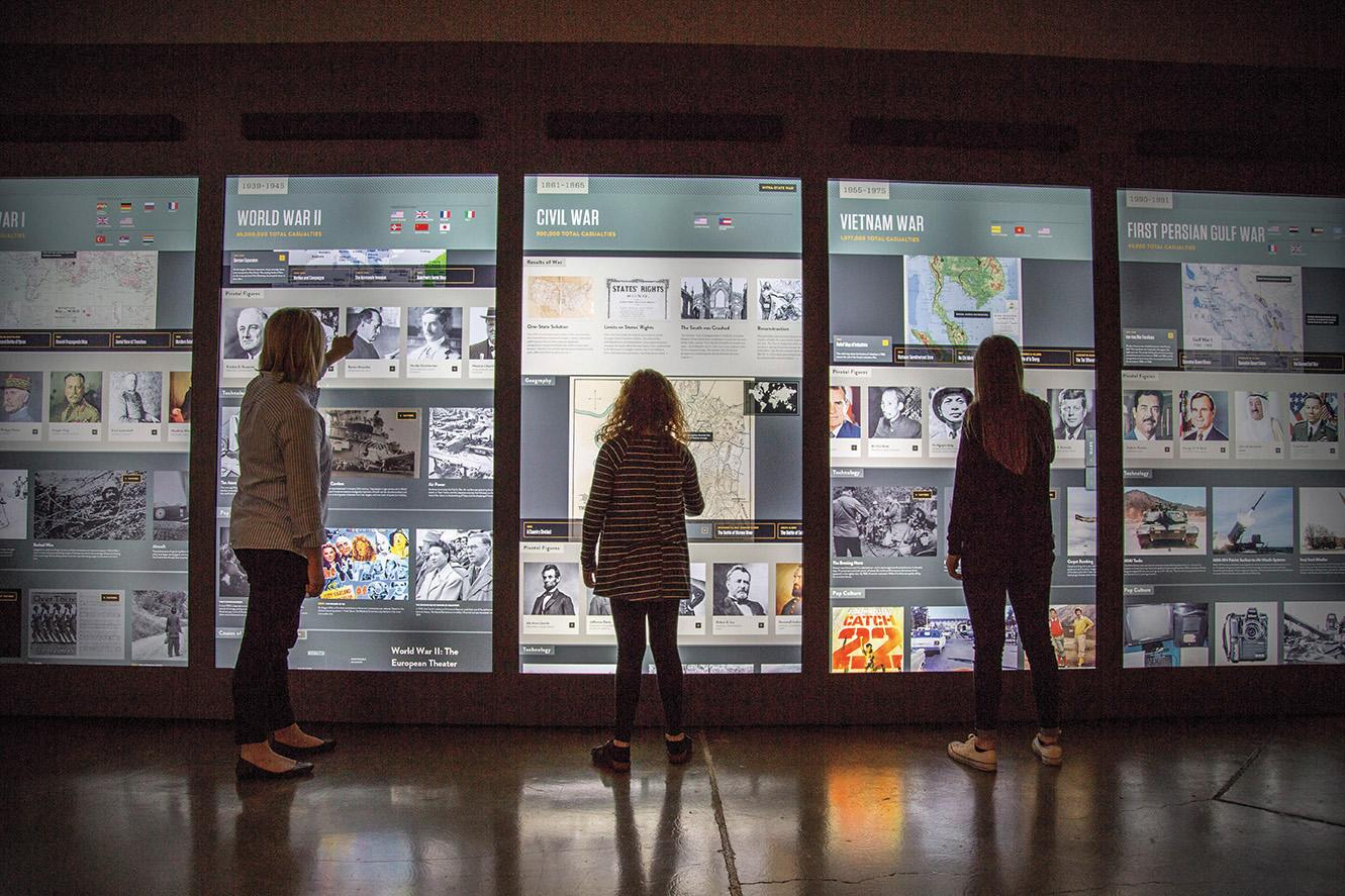 Jumbo touchscreens engage visitors in contemplating the causes of war.