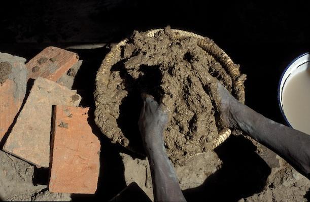 A mason prepares mud mortar.