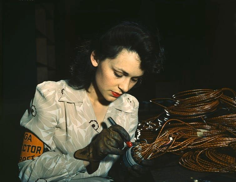 Worker at Vega Aircraft Corporation in Burbank checks electrical assemblies.