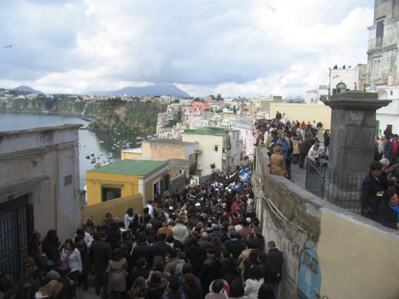 Spectators follow the procession through the fishing village of Corricella.