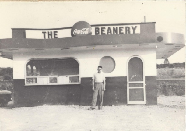 Garneau standing in front of his first curb-service restaurant, The Beanery, in 1949.
